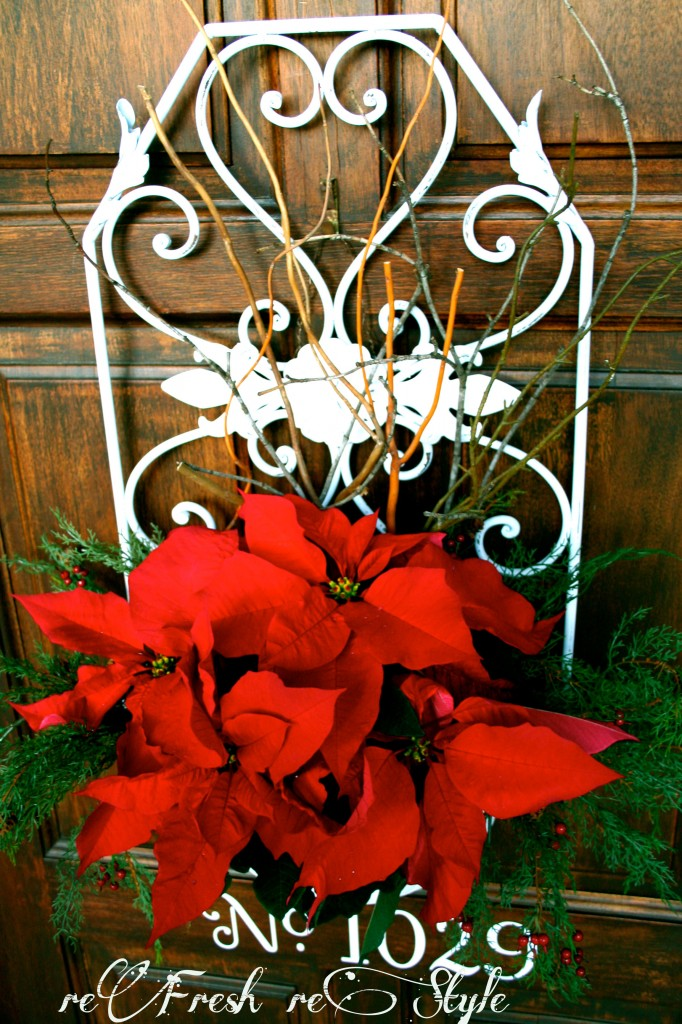 Winter door decor idea with flowers and a metal container