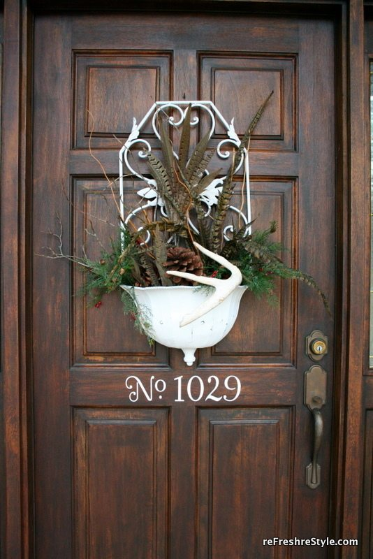 Feathers, greenery and antlers as front door decor