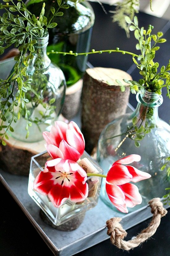Tulips on the table  with stumps and recycled wine bottles