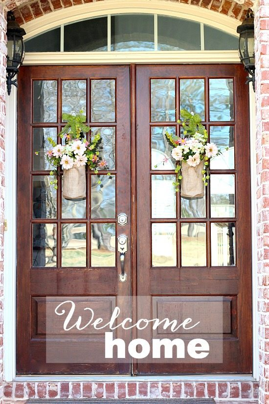 Welcome home with flowers in burlap containers.