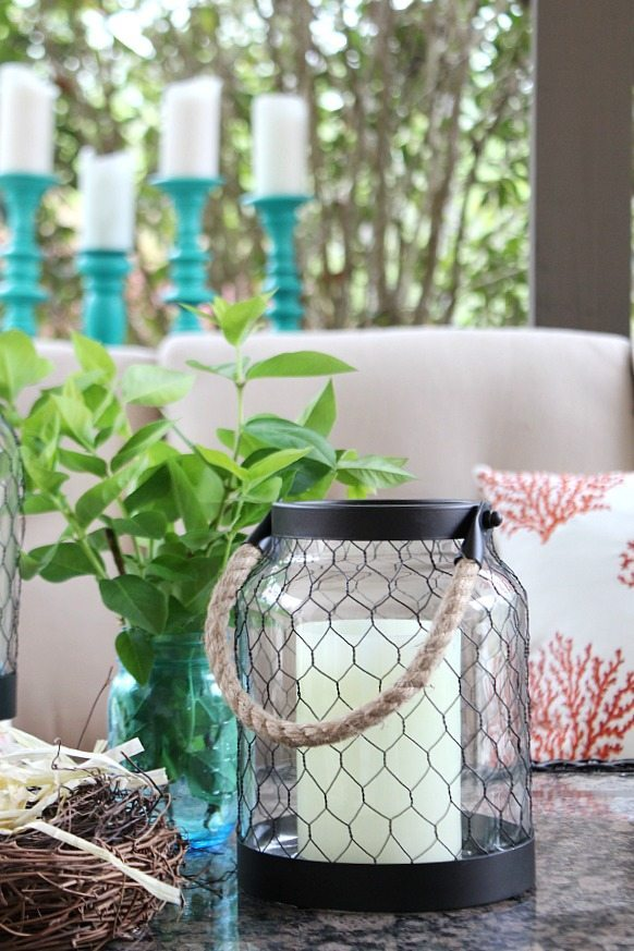 Chicken wire and rope candle holders with coral pillows and lots of teal