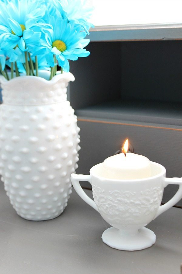 Flowers and candle in milk glass on the bedside table at refreshrestyle.com