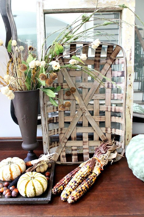 Indian Corn and woven baskets for fall in the entry at refreshrestyle.com