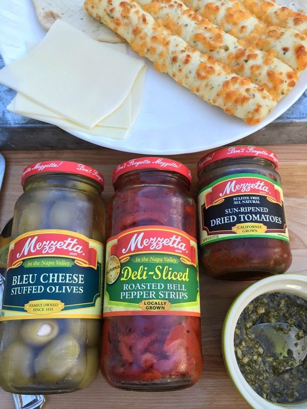 Ingredients for a quick appetizer. Pizza Bites quick and delicious with Pesto and roasted red peppers Mezzetta Olives