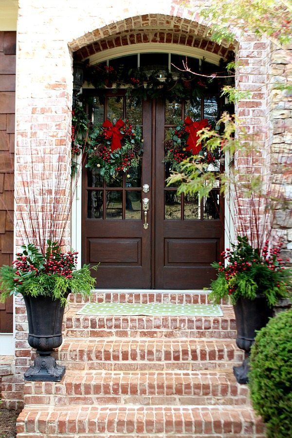 Welcome to our home at Christmas, the double doors have matching wreaths and garland above with natural elements in the flower pots.