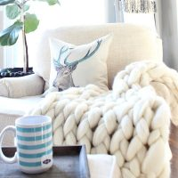 Neutral space with pops of blue and a blanket ladder for throws