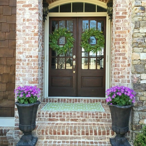 Welcome spring front door - double doors with fern wreaths - wood and windows with flowers and greenery