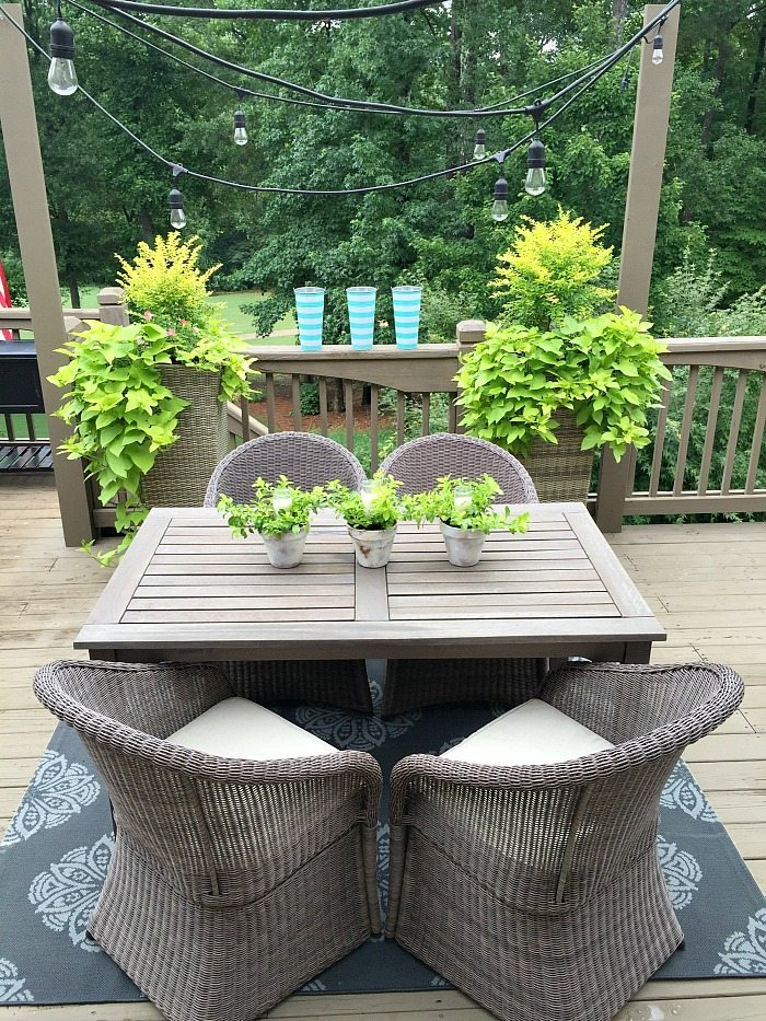 Perfect outdoor dining space with lights, candles and greenery - centerpiece of candles in garden pots