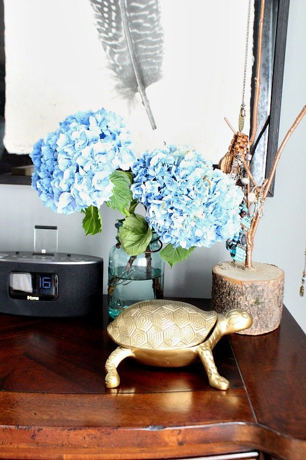 Aqua mason jar filled with hydrangeas on the night stand