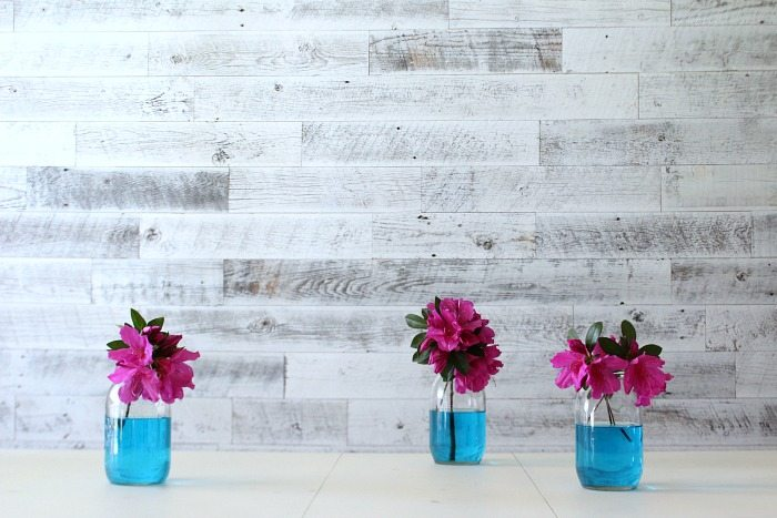 Azaleas in mason jars with blue water are perfect for the dining table