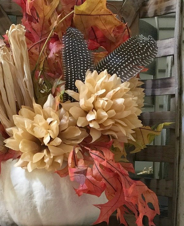Fall leaves in a white pumpkin with feathers and mums