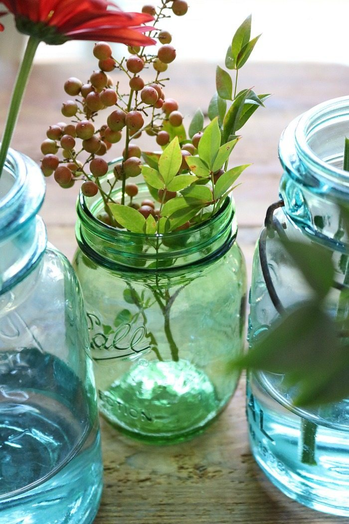 blue-and-green-mason-jars-filled-with-fall-foliage