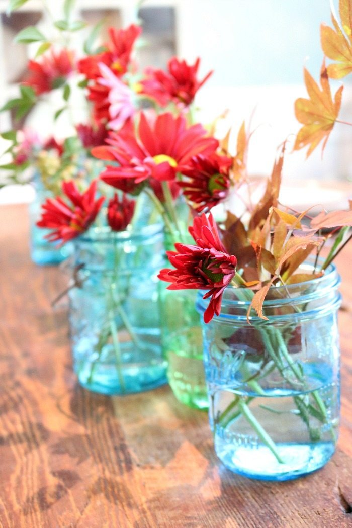 blue-mason-jars-filled-with-maple-leaves-and-mums