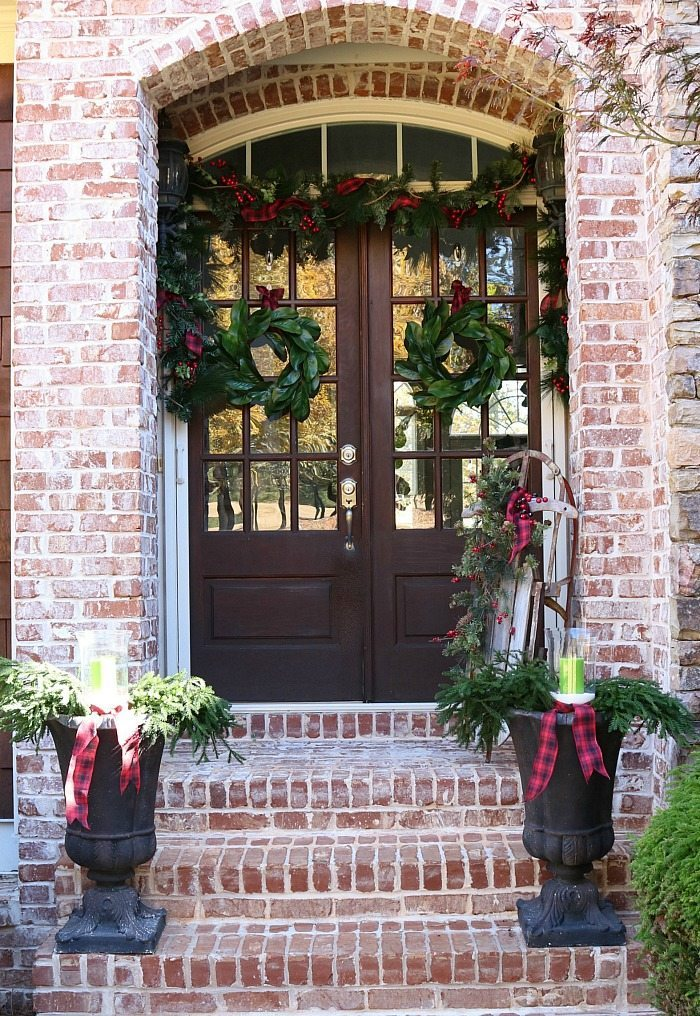 Farmhouse plaid and magnolias make a pretty Christmas Welcoming Door