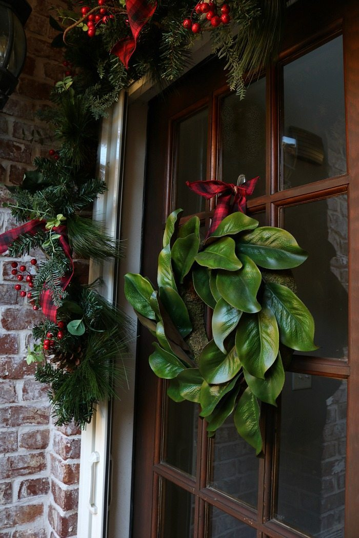 magnolia-wreath-with-plaid-ribbon-for-the-front-door-at-christmas