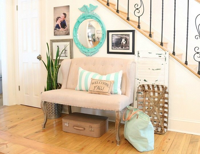 Family photos and collected thrifty items for the entry plus a turquoise federal convex mirror