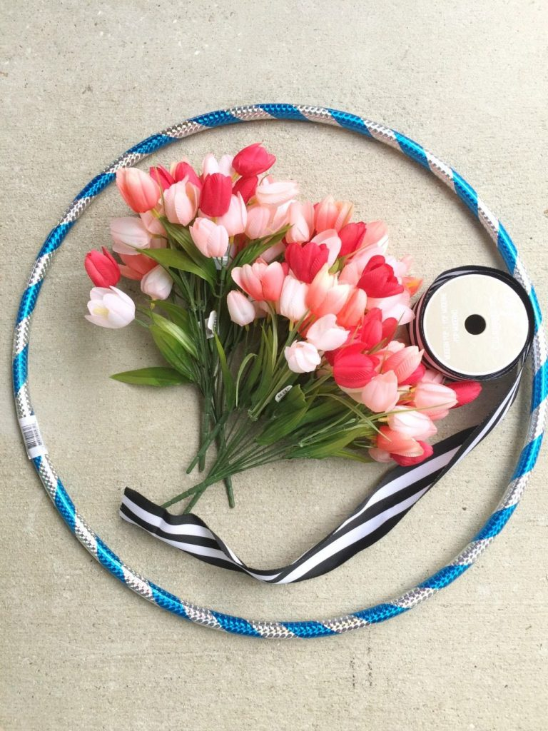 Make a hula hoop wreath with flowers and ribbon and a hula hoop