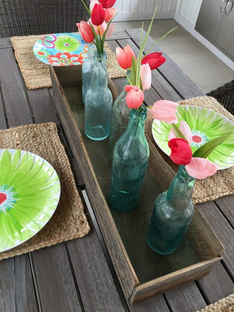farmhouse dining table with old blue bottles