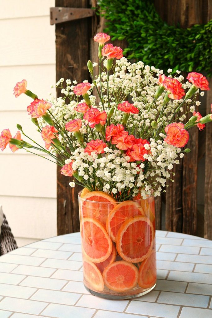 Red grapefruit and pink carnations make a sweet smelling floral arrangement