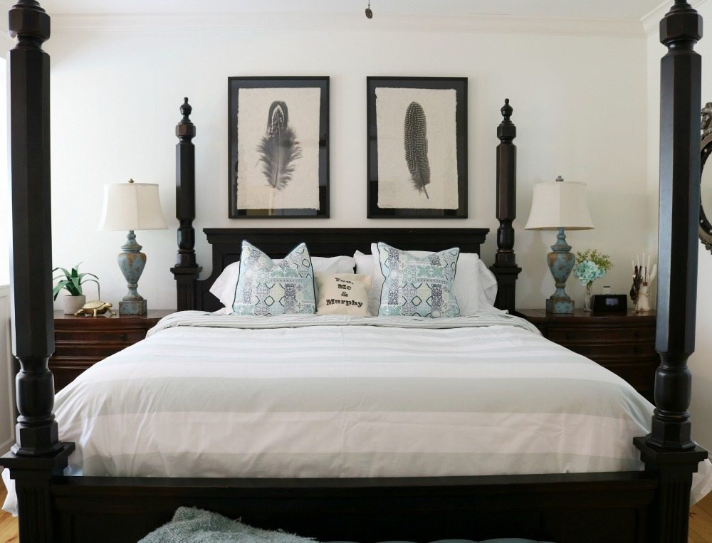 Four poster black bed with blue and white bedding