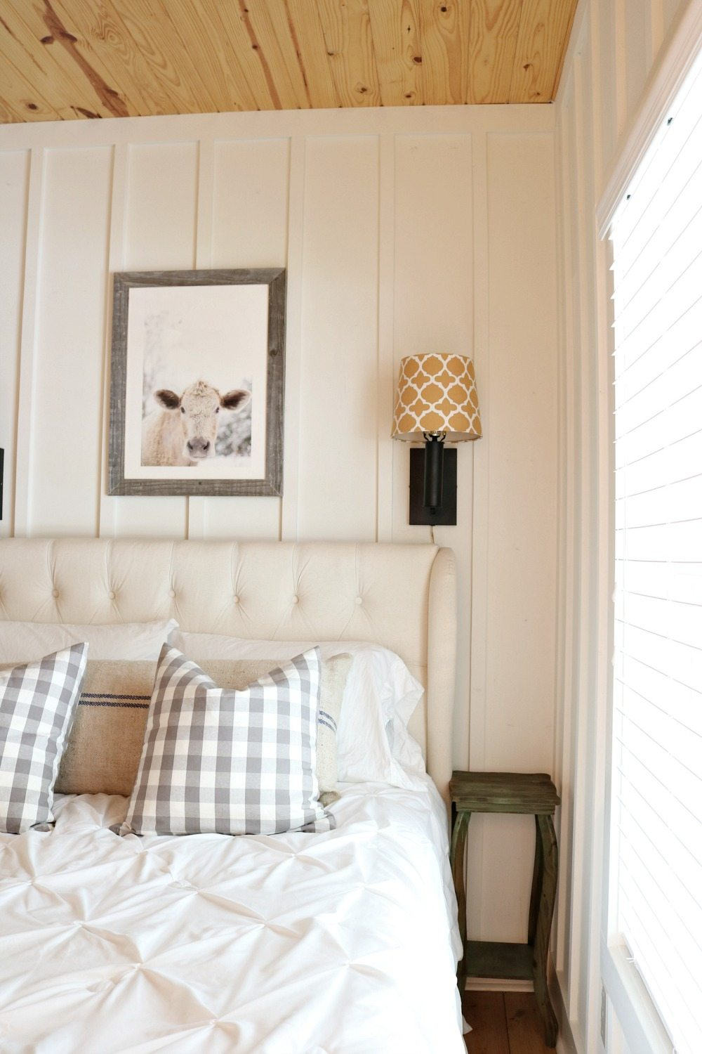 Farmhouse bedroom with lights above the bed