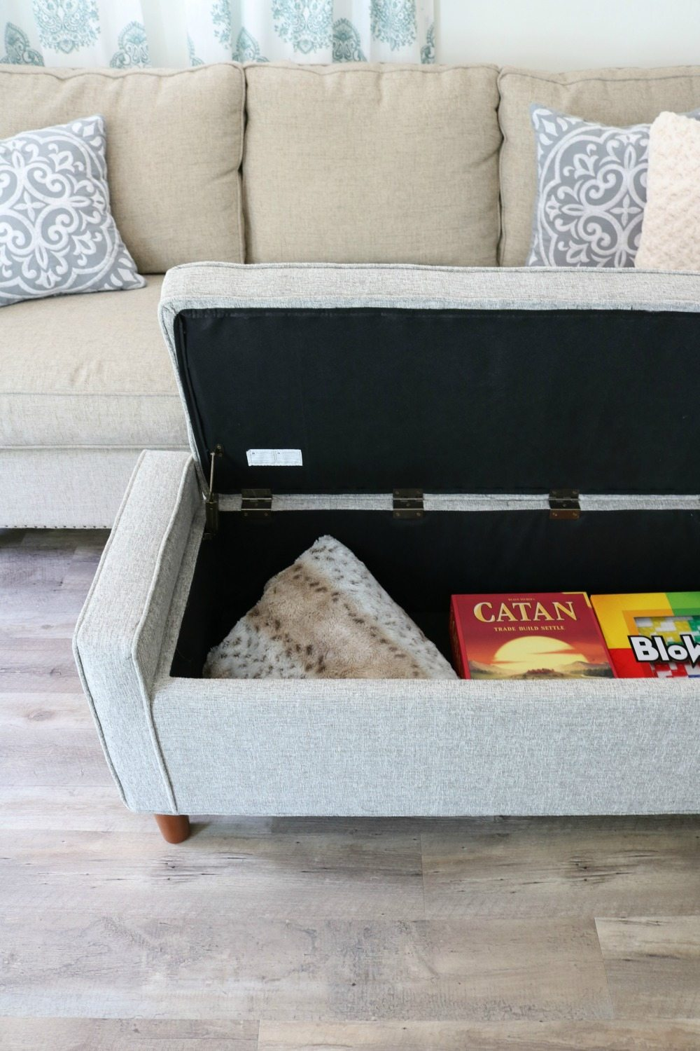 Small space living takes advantage of storage bench for living room ottoman