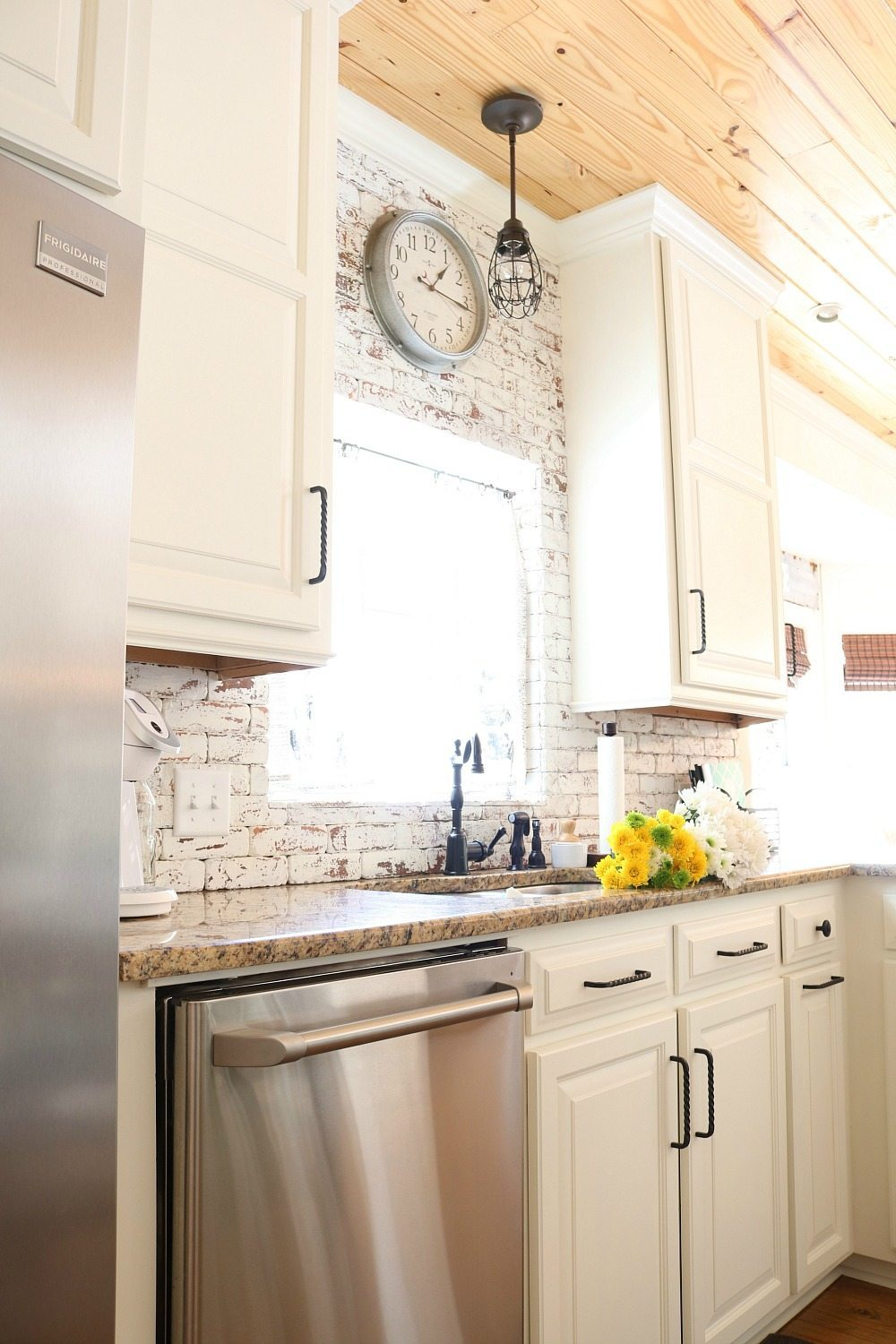 Galvanized clock on the brick wall in the kitchen at Refresh Restyle