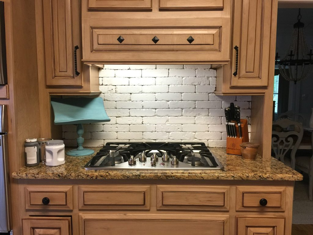Paint before sanding the brick backsplash