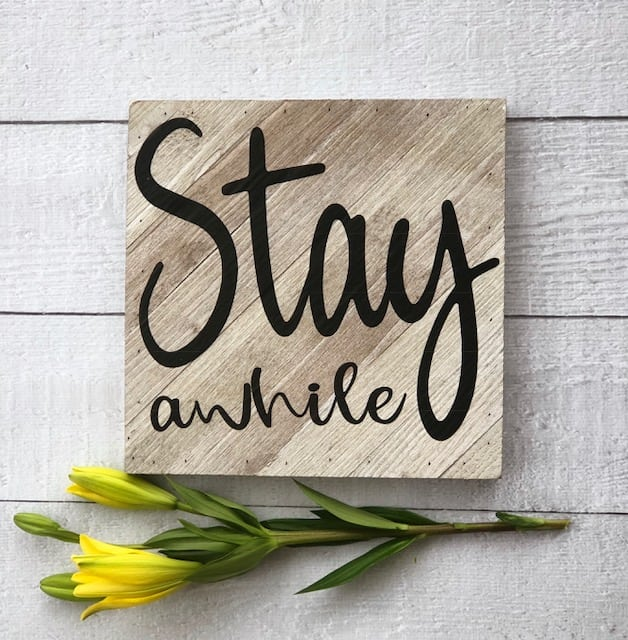 DIY this Stay A While Sign - popular farmhouse sign. It's easy with a vinyl cutting machine.