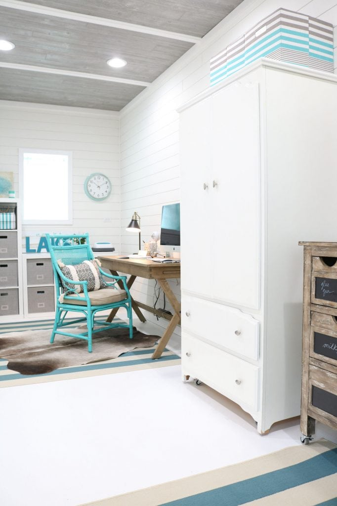 Home office in garage with shiplap and painted floors.