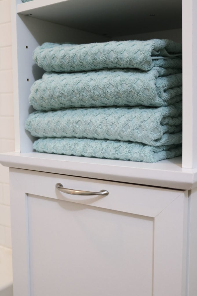 Bathroom storage with a hamper and large aqua teal towels