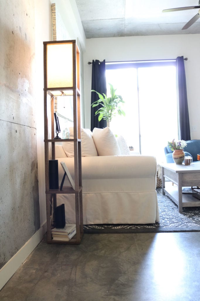 Concrete floor wall ceiling - floor lamp with shelves.